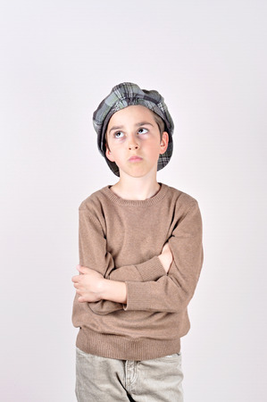 newsboy cap: Thoughtful cute young boy with newsboy cap looking up