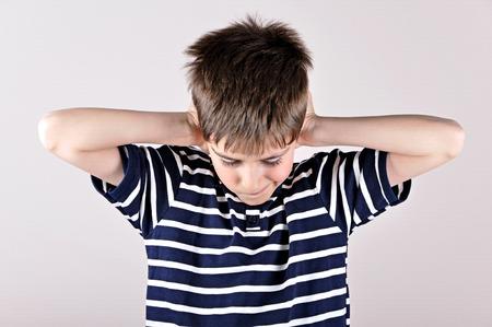 若い男の子彼の頭部を曲げ、騒音のための手で耳を覆う 写真素材