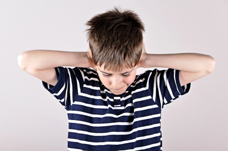 ear protection: Young boy bending his head and covering ears with hands because of loud noise Stock Photo