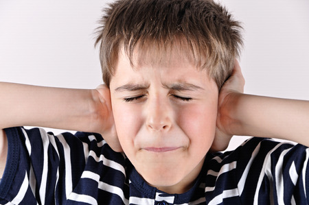ear protection: Young boy covering his ears with hands and closed mouth and eyes because of loud noise