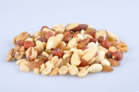 mixed nuts: Heap of mixed nuts isolated on light blue background Stock Photo