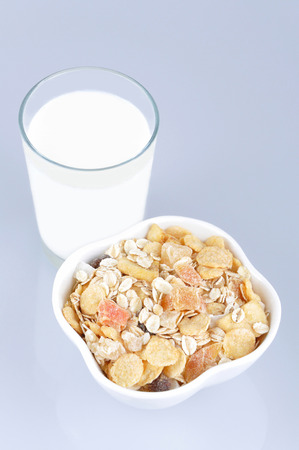 Cereals with dried and candied tropical fruit and glass of milk photo