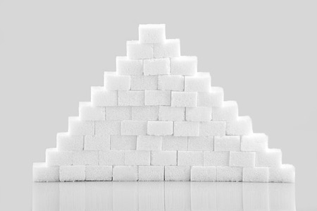Pile of sugar cubes isolated on gray background