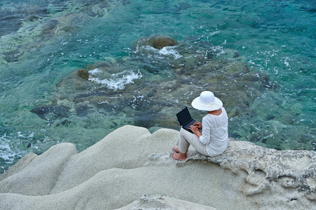 Woman wearing a hat sitting on the rock with laptop near the sea photo