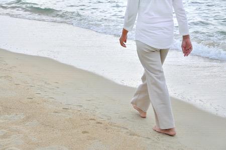 砂浜のビーチで一人歩きの女性