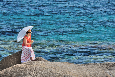 brolly: Woman with umbrella sitting on the rock near the sea
