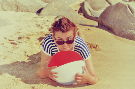 wet t shirt: Woman with a beach ball and short hair wearing sunglasses and sailor T-shirt lying on a sandy beach. Vintage style photo Stock Photo
