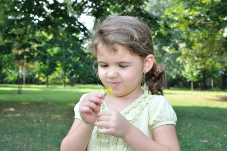 Young girl looking at a picked flowers in the city park photo