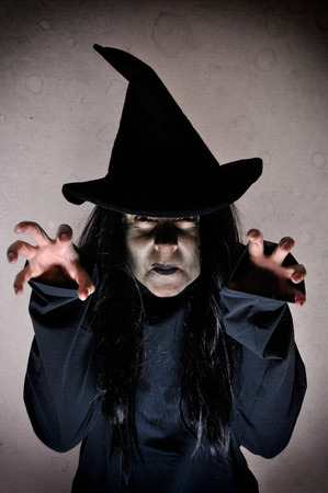 Spooky halloween witch with green face casting spells Stock Photo