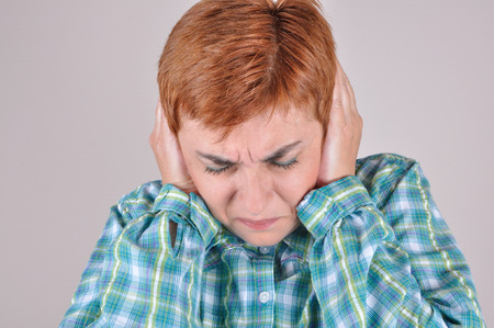 loud noise: Frowning woman with closed eyes bending her head and covering the ears with hands because of loud noise Stock Photo
