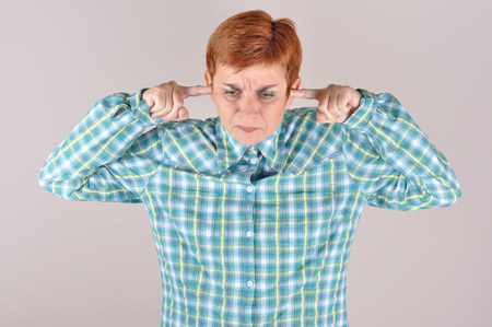 loud noise: Frowning woman holding her index fingers in her ears because of loud noise