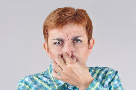 Woman holding her nose with her fingers because of  bad smell photo