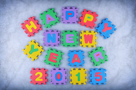 Happy New Year 2015 sign made out of alphabet and numbers puzzle pieces isolated on icy background photo