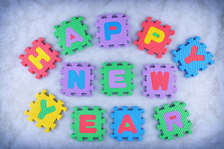 Happy New Year sign made out of alphabet puzzle pieces isolated on icy background photo