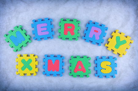 Merry Christmas sign made out of alphabet puzzle pieces isolated on icy background photo