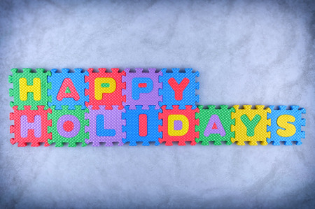 Happy Holidays sign made out of alphabet puzzle pieces isolated on icy background photo