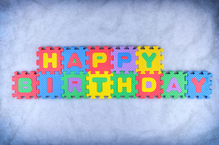 Happy Birthday sign made out of alphabet puzzle pieces photo