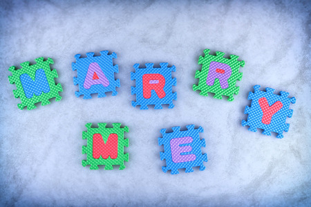 Marry me sign made out of alphabet puzzle pieces photo