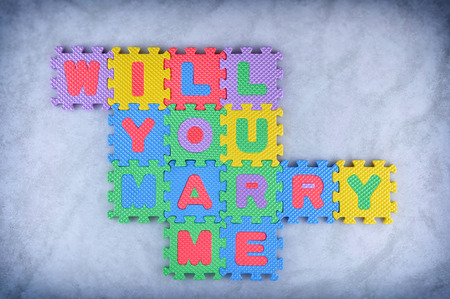 Will you marry me sign made out of alphabet puzzle pieces photo