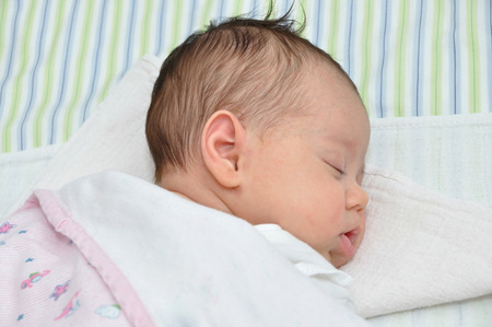 Cute newborn baby girl sleeping in bed photo