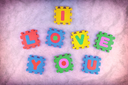 I love you sign made out of alphabet puzzle pieces isolated on pink background photo