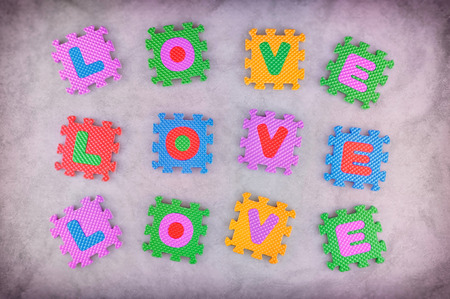 Love sign made out of alphabet puzzle pieces isolated on pink background photo