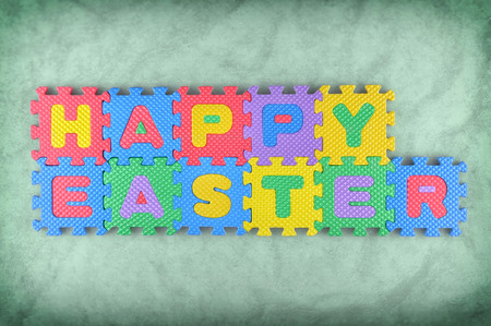 Happy Easter sign made out of alphabet puzzle pieces isolated on the green background photo