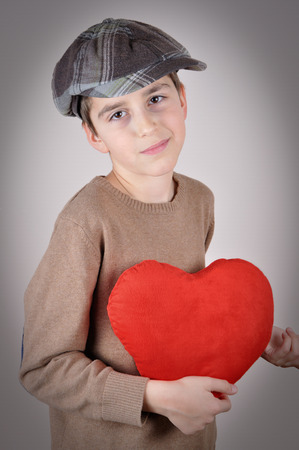 newsboy cap: Cute young boy with newsboy cap holding a plush red heart on Valentine?s day