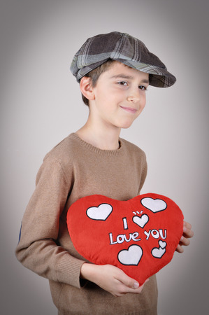 newsboy cap: Cute young boy with newsboy cap holding a plush red heart with I love you message on Valentine?s day Stock Photo