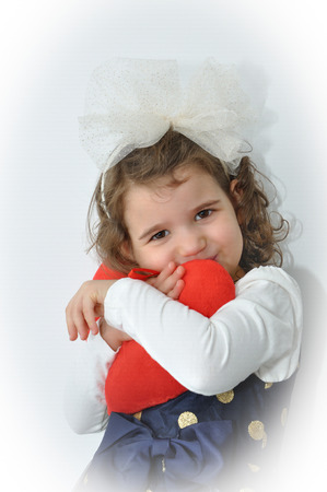 alice band: Cute young girl with alice band with a white bow holding a plush red heart on Valentine?s day