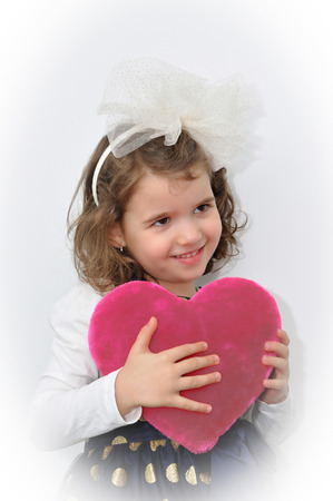 alice band: Cute young girl with alice band with a white bow holding a plush pink heart on Valentine?s day
