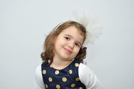 alice band: Portrait of a cute young girl wearing a blue dress with gold spots and alice band with a white bow