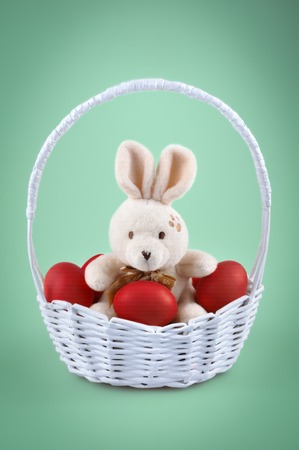 Easter bunny with red eggs in the basket isolated on the green background photo