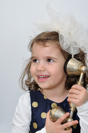 Cute young girl wearing a blue dress with gold spots and alice band with a white bow talking on the retro telephone photo