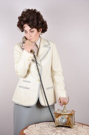 disconnecting: Thoughtful worried woman holding the receiver of the retro telephone on her shoulder and disconnecting the line Stock Photo