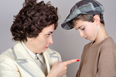 Woman scolding and pointing her index finger at the young boy. Vintage style photo