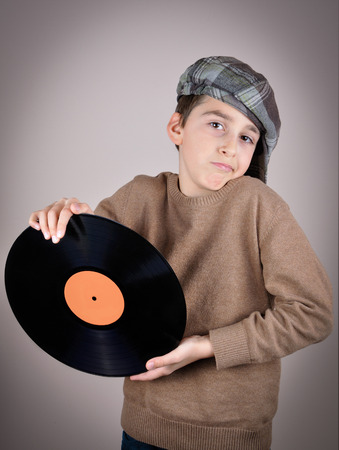 newsboy cap: Surprised and amazed cute young boy wearing a brown sweater and tartan newsboy cap holding and showing a vinyl record. Isolated on gray background and added vignette. Vintage style photo Stock Photo