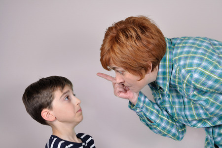 angry teacher: Woman scolding and pointing her index finger at the scared young boy Stock Photo