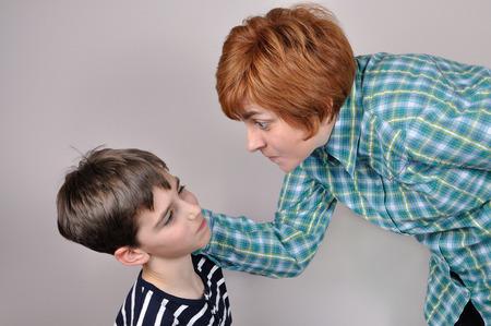 女性の叱責と怖がって若い男の子の耳を引っ張って 写真素材