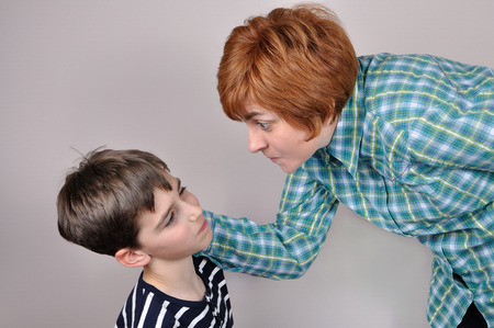 angry kid: Woman scolding and pulling the ear of the scared young boy