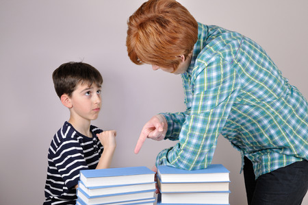Nervous and angry woman scolding a surprised young boy and showing him how many books he has to read