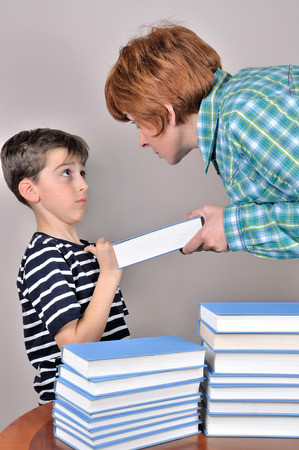 Nervous and angry woman scolding a surprised young boy and showing him a book he has to read photo