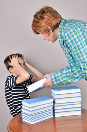 angry teacher: Nervous and angry woman scolding a surprised young boy and showing him a book he has to read
