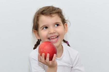 二つのおさげと赤いリンゴを保持して美しい白い歯甘い少女の笑みを浮かべてください。
