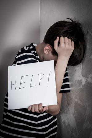 手書きヘルプ記号の付いた紙を開いて怖いと虐待の若い男の子。低いキー 写真素材