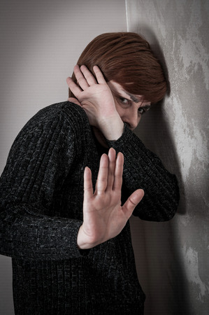 abused: Scared and abused woman with one hand one the head and the other arm stretched. Low key Stock Photo