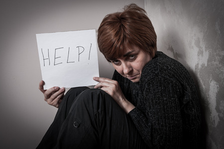 abused: Scared and abused woman holding the paper with handwritten help sign. Low key Stock Photo