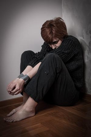 violencia intrafamiliar: Miedo mujer, atrapada y abusado con las manos atadas. Baja clave