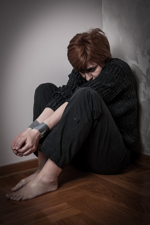 domestic violence: Scared, trapped and abused woman with tied hands. Low key