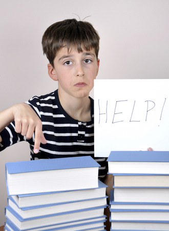 Sad, disappointed and depressed  young boy sitting at the table with books and holding the paper with handwritten help sign. Boy showing with his index finger how many books he has to read photo